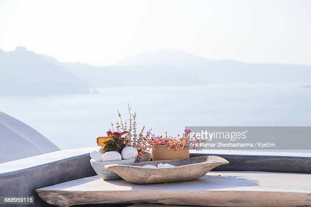 Flowers Decoration On Table Against Sea At Santorini Island During Foggy Weather