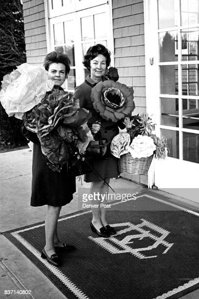 Flowers For Country Club Fiesta Mrs Walter Steele left and Mrs Donald Peterson are laden with bright Mexican paper flowers as they arrive at the...
