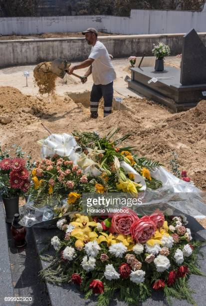 Flowers from a recent burial of a fire victim are seen in the foreground while an undertaker digs one of the graves for the victims of the forest...