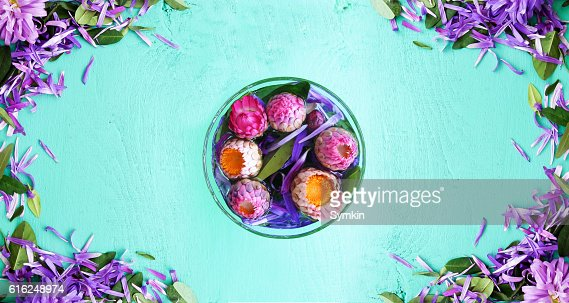 Flowers in a glass in the middle of the table : Stock Photo