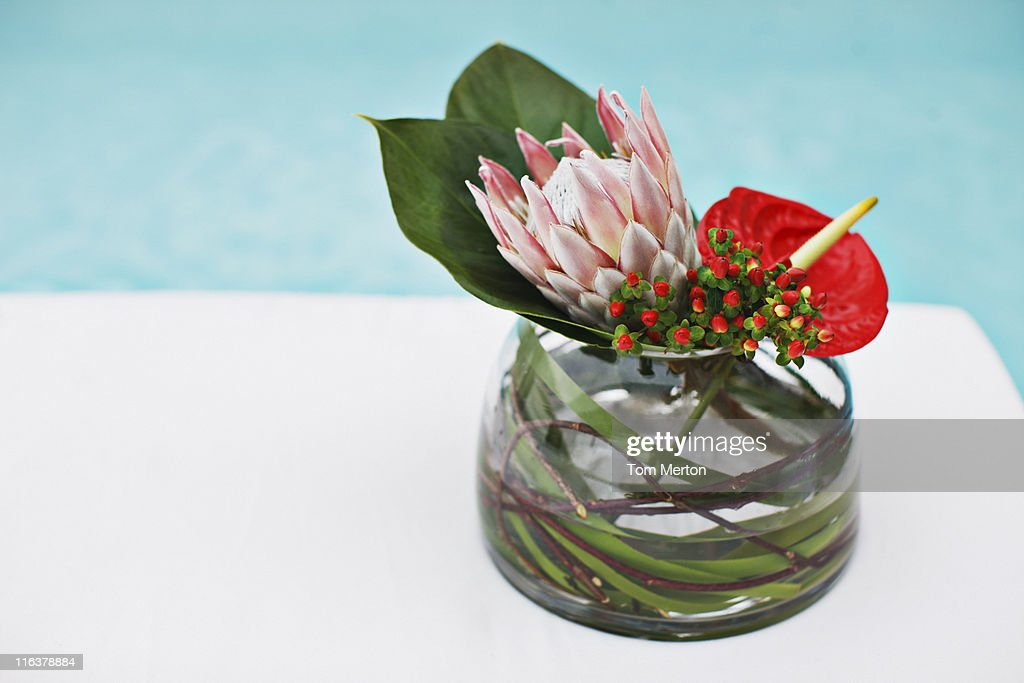 Flowers in vase at poolside : Stock Photo