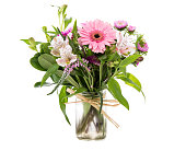 Beautiful Bouquet of pink Gerbera Daisies and purple and white wild flowers in clear glass vase Isolated on white background