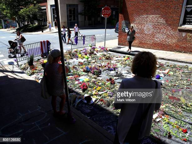Flowers lay on the street where Heather Heyer was killed and 19 others injured when a car slammed into a crowd of people protesting against a white...
