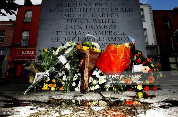Flowers left at the memorial on Talbot Street to the 1974 Dublin and Monaghan Bombings on the anniversary day of the bombings run water onto the...