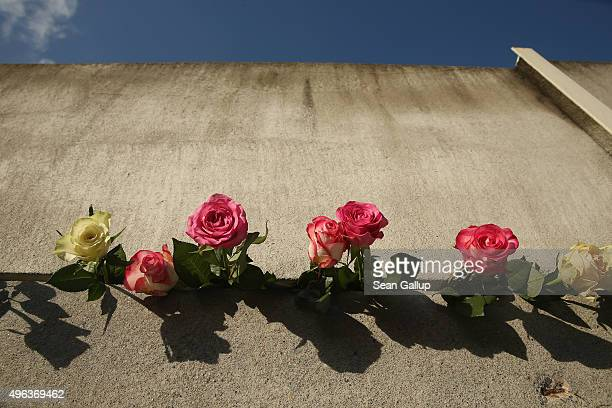 Flowers left by visitors lie stuck between concrete slats at the Berlin Wall memorial at Bernauer Strasse on the 26th anniversary of the fall of the...