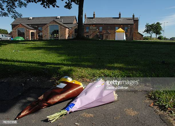 Flowers left in codolance are seen as police erect a tent to conceal the area where elevenyearold Rhys Jones was shot by a youth on a BMX bicycle on...