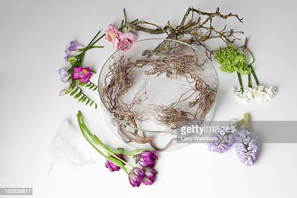 Flowers lying on a table around a glass bowel vase