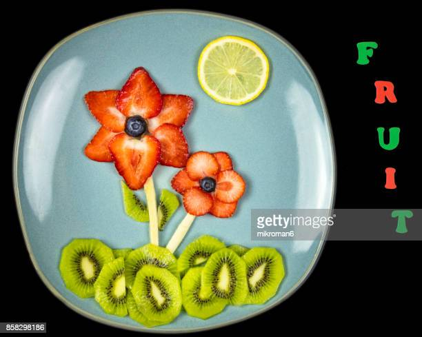 Flowers made with fresh fruits and FRUIT text. Fruit Art Recipe. Food art creative concepts.