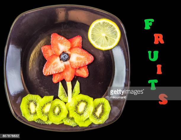 Flowers made with fresh fruits and FRUITS text. Fruit Art Recipe. Food art creative concepts.