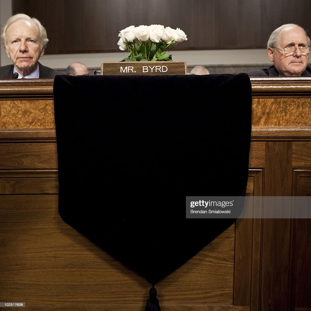 Flowers occupy the seat of U.S. Sen. Robert Byrd (D-WV), who died yesterday at the age of 92, as U.S. Sen. <a gi-track='captionPersonalityLinkClicked' href=/galleries/search?phrase=Joseph+Lieberman&family=editorial&specificpeople=236098 ng-click='$event.stopPropagation()'>Joseph Lieberman</a> (I-CT) (L) and committee chairman U.S. Sen. <a gi-track='captionPersonalityLinkClicked' href=/galleries/search?phrase=Carl+Levin&family=editorial&specificpeople=208878 ng-click='$event.stopPropagation()'>Carl Levin</a> (D-MI) (R) sit on either side during a confirmation hearing for U.S. Gen. David Petraeus, before the Senate Armed Services Committee on Capitol Hill June 29, 2010 in Washington, DC. Petraeus, the commander of U.S. forces in the Middle East, has been appointed by U.S. President Barack Obama to replace U.S. Gen. Stanley McCrystal as commander of the United States Forces Afghanistan.