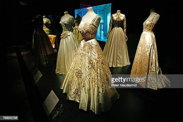 'Flowers of the Fields of France' a ceremonial gown designed for HM Queen Elizabeth II by Norman Hartnell from 1957 is displayed with another gown by...