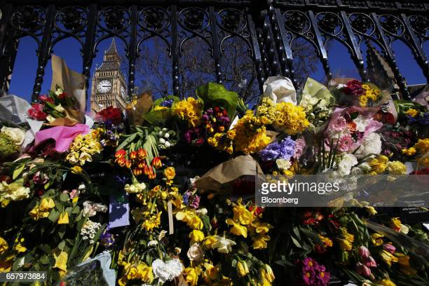 Flowers placed in memory of those who died in the Westminster terror attack sit on the perimeter fence of the Houses of Parliament during a Unite for...