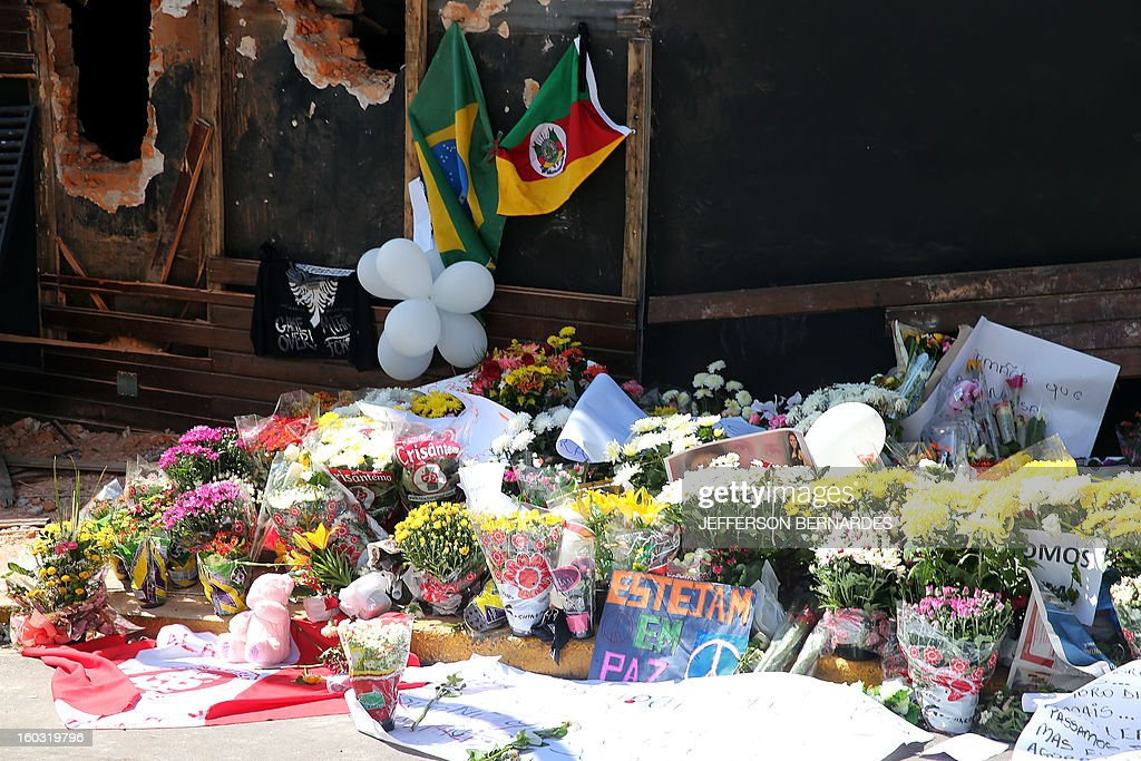 Flowers put in front of the Kiss nightclub in Santa Maria, southern Brazil on January 29, 2013 where a blaze Sunday early morning left a death toll of over 230. Police in Brazil arrested four suspects Monday after a nightclub fire killed 231, left dozens more clinging to life, and forced officials to defend readiness for the Olympics and World Cup.