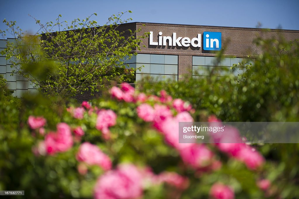 Flowers stand in front of LinkedIn Corp. signage displayed on the facade of the company's headquarters in Mountain View, California, U.S. on Thursday, April 25, 2013. LinkedIn Corp. added publishing platform Pulse, a news-reading application used by more than 20 million people in 190 countries, for news and content this month. Photographer: David Paul Morris/Bloomberg via Getty Images