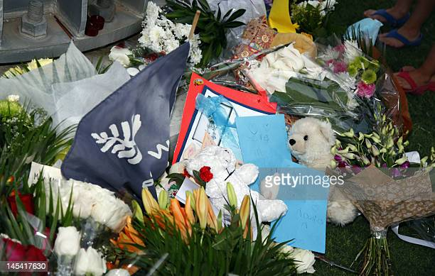 Flowers toys and candles are laid as mourners gathered at the 'Aspire Zone' close to the scene where twoyearold New Zealand triplets among 19 others...