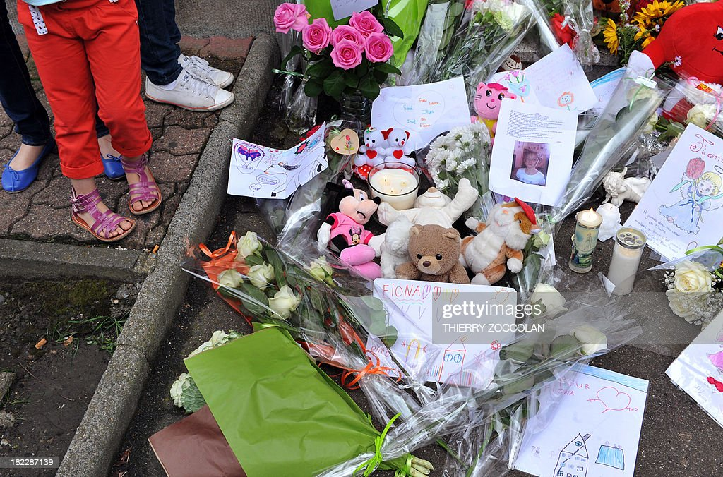 Flowers, toys and messages are left outside the house where five-year-old Fiona used to live in Clermont-Ferrand on September 29, 2013. French police are still searching for the body of Fiona whose mother, who was taken into questioning with her partner, admitted to investigators that the girl had died and her body was at the edge of a forest.