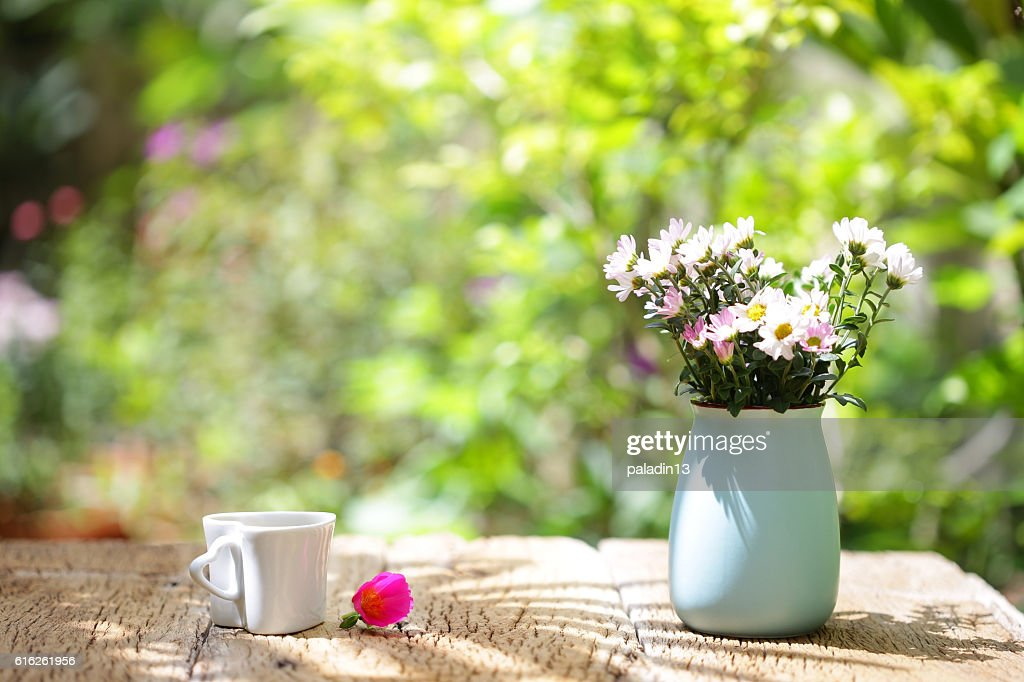 Flowers vintage pot and heart shaped cup on wooden table : Stock Photo