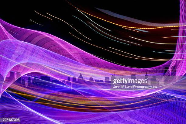Flowing multicolor abstract light beams over city skyline