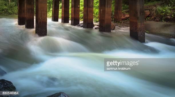Flowing river under concrete bridge