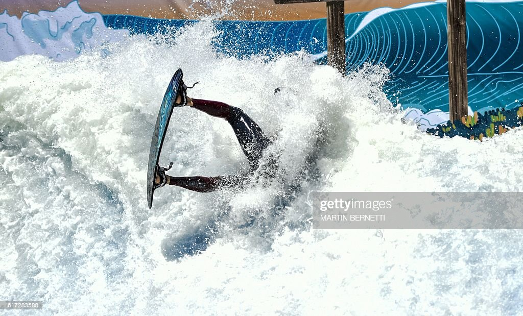 A flowrider competes on an artificial wave, during the Flow Tour 2016 in Santiago on October 22, 2016. Artificial waves are created by powerful pumps that throw thousands of liters of water against a wall. The size of the wave can be regulated to suit the skills of the surfer and can reach a height up to three meters. / AFP / MARTIN