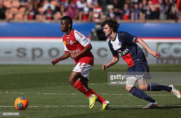 Floyd Ayite of Stade de Reims and Adrien Rabiot of PSG in action during the french Ligue 1 match between Paris SaintGermain FC and Stade de Reims at...