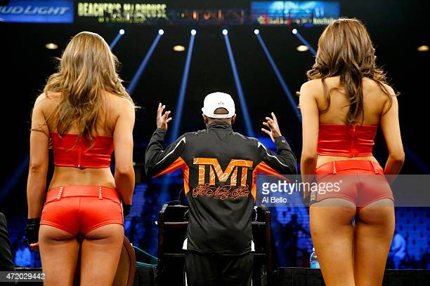 Floyd Mayweather Jr addresses the media as he stands between the Tecate girls during the postfight news conference after his unanimous decision...