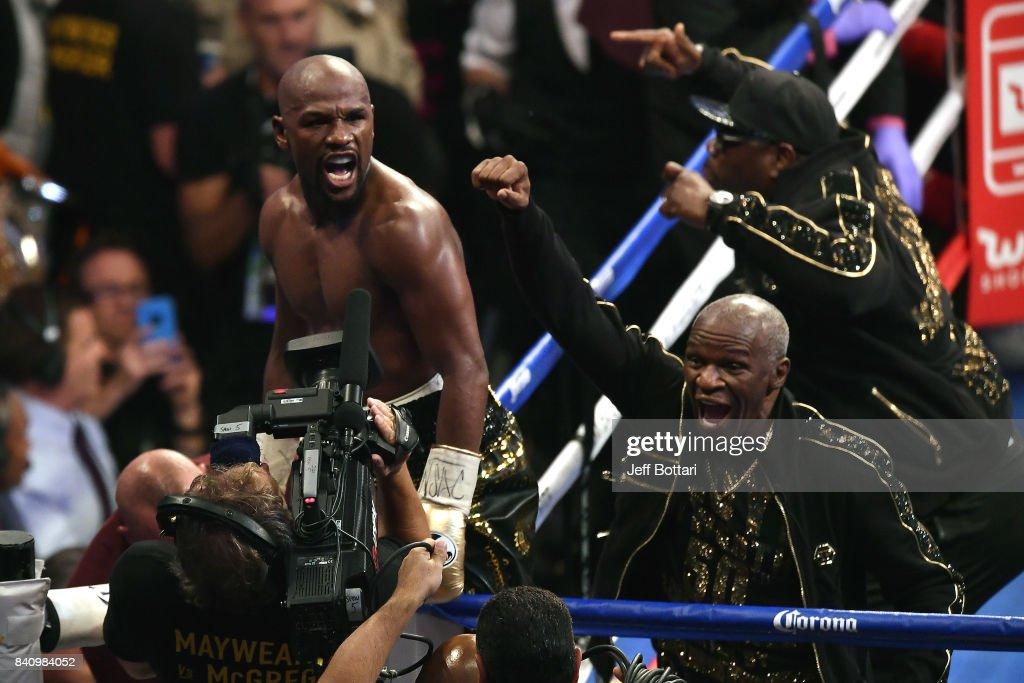 Floyd Mayweather Jr. (L) and Floyd Mayweather Sr. celebrate after defeating Conor McGregor in their super welterweight boxing match at T-Mobile Arena on August 26, 2017 in Las Vegas, Nevada. Mayweather won by 10th-round TKO.