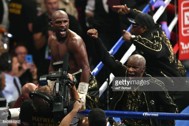 Floyd Mayweather Jr and Floyd Mayweather Sr celebrate after defeating Conor McGregor in their super welterweight boxing match at TMobile Arena on...