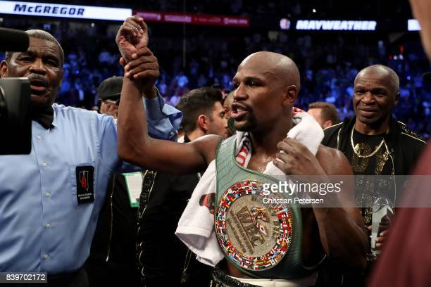 Floyd Mayweather Jr celebrates with the WBC Money Belt after his TKO of Conor McGregor in their super welterweight boxing match on August 26 2017 at...