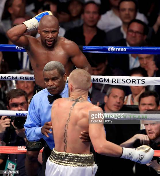 Floyd Mayweather Jr holds the back of his head as referee Robert Byrd pushes Conor McGregor away during their super welterweight boxing match on...