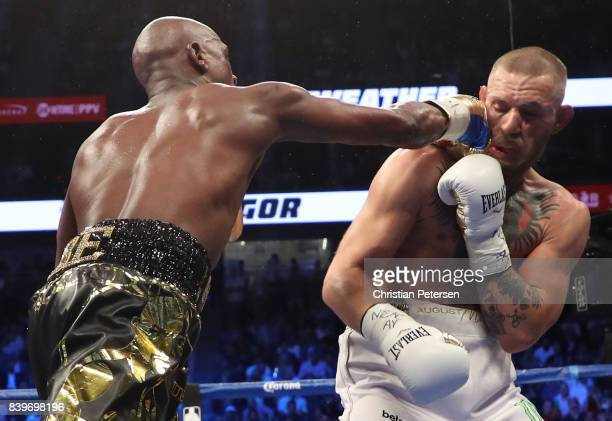 Floyd Mayweather Jr throws a punch at Conor McGregor during their super welterweight boxing match on August 26 2017 at TMobile Arena in Las Vegas...