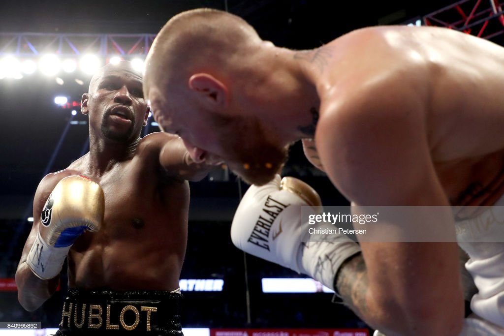 Floyd Mayweather Jr. throws a punch at Conor McGregor during their super welterweight boxing match on August 26, 2017 at T-Mobile Arena in Las Vegas, Nevada.