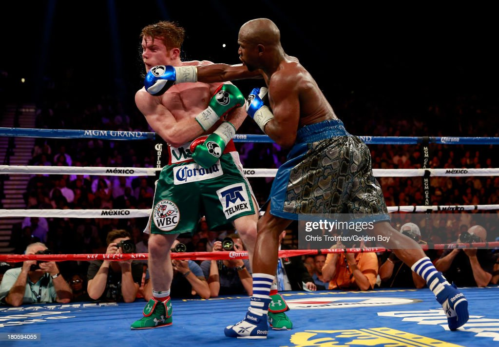 Floyd Mayweather Jr. throws a right to the head of Canelo Alvarez during their WBC/WBA 154-pound title fight at the MGM Grand Garden Arena on September 14, 2013 in Las Vegas, Nevada.