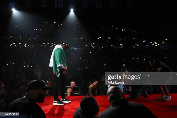 Floyd Mayweather Jr walks to the stage wearing the flag of Ireland during the Floyd Mayweather Jr v Conor McGregor World Press Tour event at Barclays...