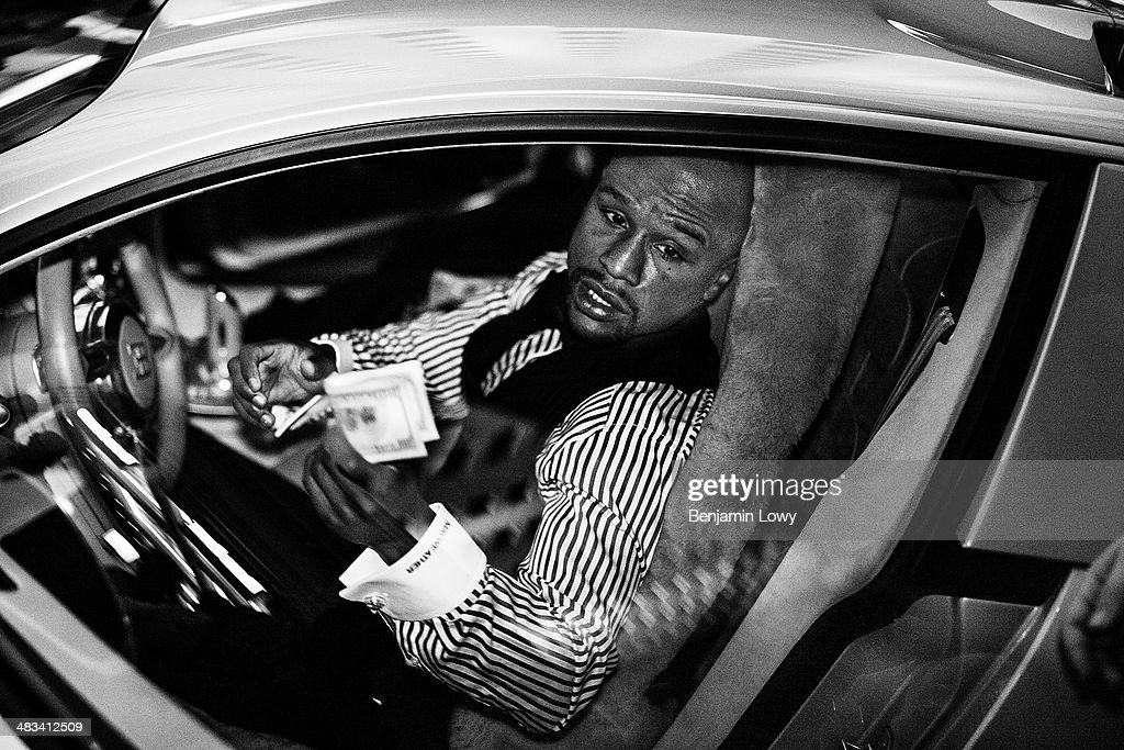 Floyd Mayweather tips a valet from his car in front of a casino on August 10, 2013, in Las Vegas, Nevada, before his fight with Saul Alvarez, a Mexican boxer known as El Canelo.