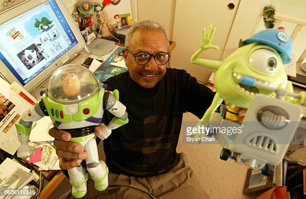 Floyd Norman holds up Buzz Lightyear and Mike Wazowski toys from the movies Toy Story and Monsters Inc respectively that he worked on as an animator...