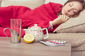 Sick woman covered with a blanket lying in bed with high fever and a flu, resting. Teapot, pills and lemon on the table, focus on the lemon and a teapot