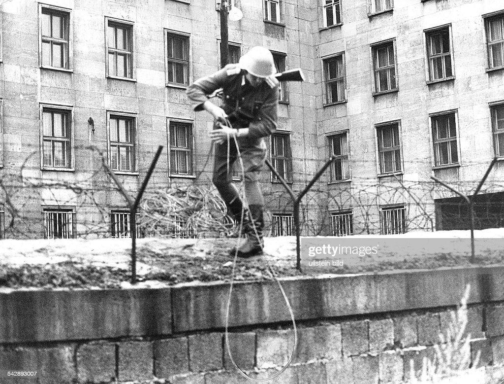 Flucht der Familie Holzapfel vom Haus der Ministerien (Ostberlin) nach Westberlin:Ein Volkspolizist ist auf die Mauergeklettert, um das Fluchtseil aufOstberliner Gebiet zu ziehen- 1965