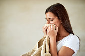 Shot of young woman enjoying the smell of freshly washed towels