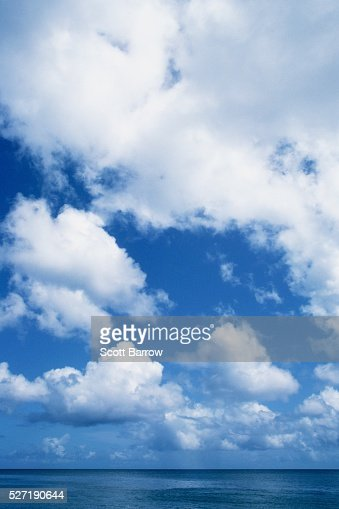 Fluffy clouds over the ocean : Stock Photo