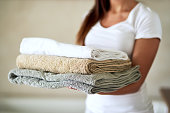 Shot of an unidentifiable woman holding a pile of clean towels