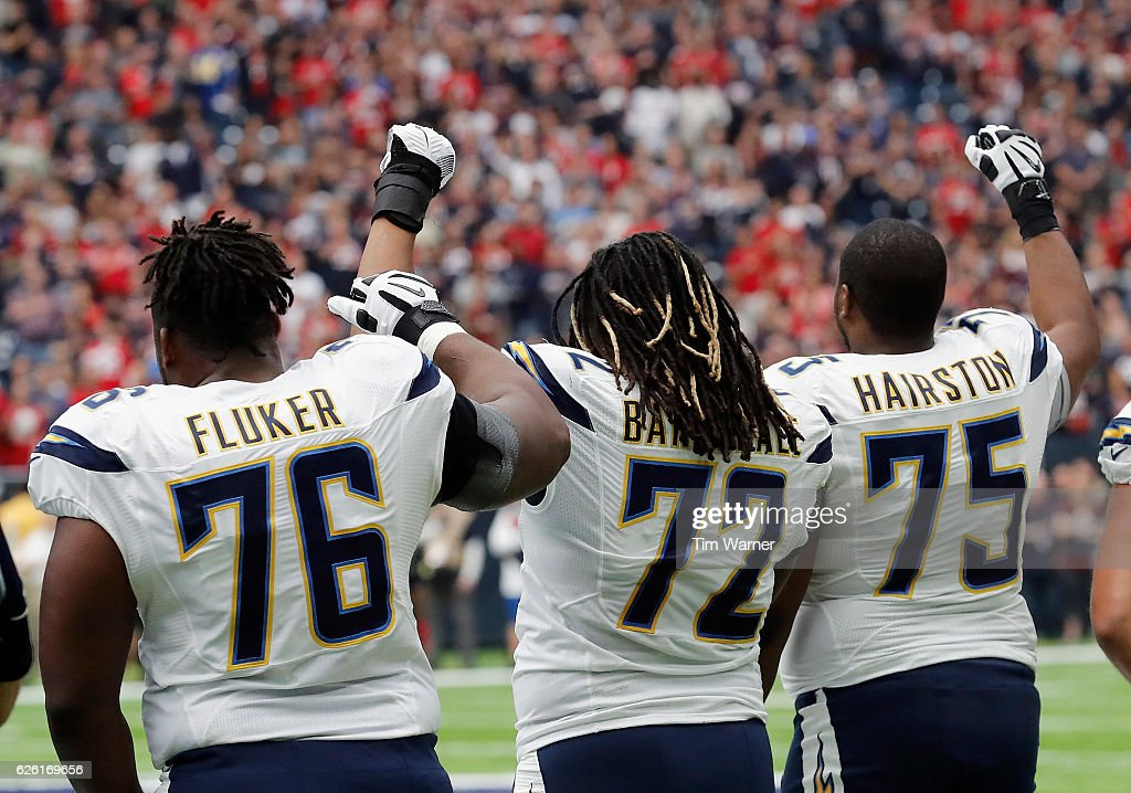 D.J. Fluker #76, Joe Barksdale #72, and Chris Hairston #75 of the San Diego Chargers raise their fists during the National Anthem before the game against the Houston Texans at NRG Stadium on November 27, 2016 in Houston, Texas.