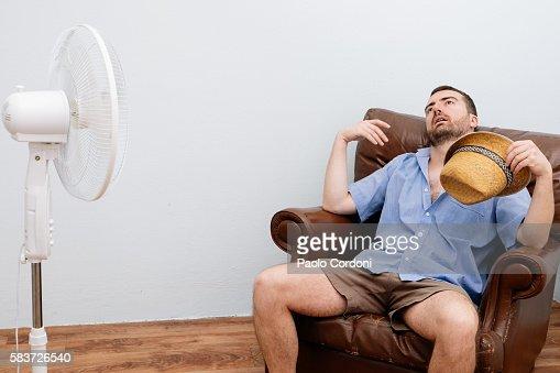 Flushed man feeling hot in front of a fan : Foto de stock