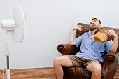 Flushed man feeling hot in front of a fan
