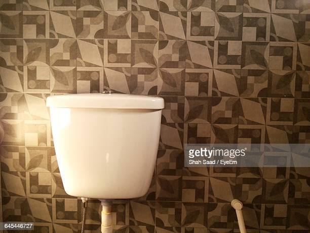 Flushing Toilet Against Pattered Wall In Bathroom