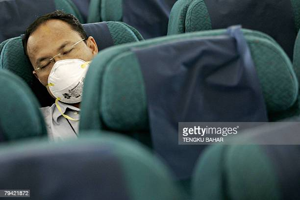 A 'flustricken' passenger sits among empty seats after being isolated from other passengers for flu symptoms during a pandemic influenza response...
