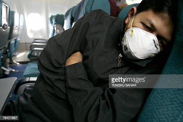 A 'flustricken' passenger wearing a face mask huddles up after being isolated from other passengers for flu symptoms during a pandemic influenza...