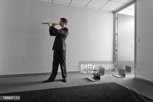 Flute player conducting laptops : Stock Photo