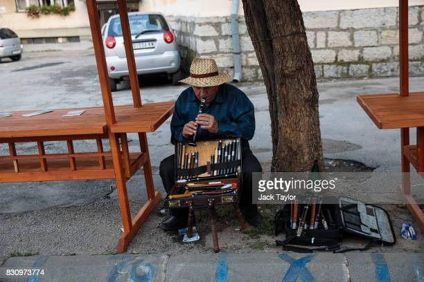 A flute seller plays a tune on the street in the town centre during the Guca Trumpet Festival on August 11 2017 in Guca Serbia Thousands of revellers...