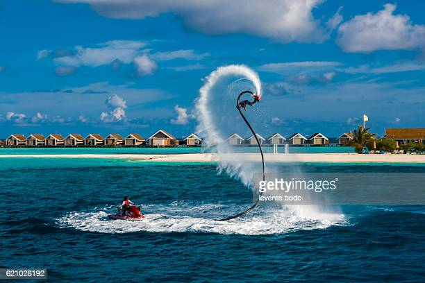 Fly board and jet ski in the blue lagoon. Silhouette of a fly board rider at sea. Professional rider is playing with a new water sport called fly board. Tropical summer water-sport activity.